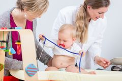 Cute and healthy baby girl playing with the stethoscope during routine check-up stock photo