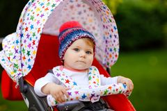 Cute healthy little beautiful baby girl with blue warm hat sitting in the pram or stroller and waiting for mom. Happy royalty free stock image