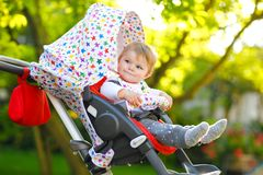 Cute healthy little beautiful baby girl sitting in the pram or stroller and waiting for mom. Happy smiling child with stock photo