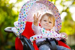 Cute healthy little beautiful baby girl sitting in the pram or stroller and waiting for mom. Happy smiling child with royalty free stock photography