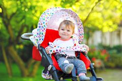 Cute healthy little beautiful baby girl sitting in the pram or stroller and waiting for mom. Happy smiling child with royalty free stock image