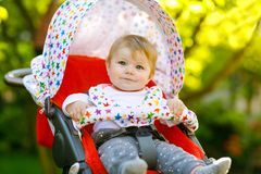Cute healthy little beautiful baby girl sitting in the pram or stroller and waiting for mom. Happy smiling child with royalty free stock photos