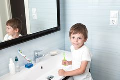 Cute healthy little child holding toothbrush in the bathroom royalty free stock image