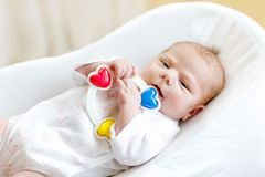 Cute healthy newborn baby playing with colorful rattle toy. in white bed at home. New born child, little girl looking. Surprised at the camera. Family, new life royalty free stock photos