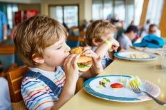 Cute healthy preschool boy eats hamburger sitting in school canteen stock photography
