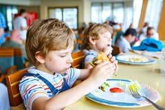Cute healthy preschool boy eats hamburger sitting in school canteen stock photo