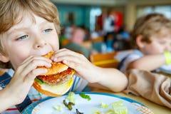 Cute healthy preschool boy eats hamburger sitting in school canteen Royalty Free Stock Photography