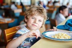 Cute healthy preschool boy eats pasta sitting in school canteen. Cute healthy preschool kid boy eats pasta noodles sitting in school or nursery cafe. Happy child stock photography
