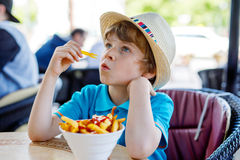 Cute healthy preschool kid boy eats french fries potatoes with ketchup Stock Image