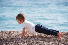 Cute healthy strong kid making pushups with effort on sea coast in autumn royalty free stock photo
