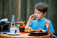 Cute healthy teenager boy eats hamburger and potato Stock Images