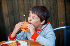 Cute healthy teenager boy eats hamburger Stock Photography