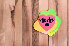 Cute heart beauty emoji. Drawing beauty emoji in heart shaped sticky note on wood background stock photos