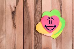 Cute heart Laugh emoji. Drawing Laugh emoji in heart shaped sticky note on wood background stock image
