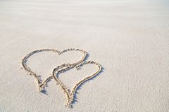 Heart shape drawing in the sand on tropical beach, romantic and honeymoon concept background for couples. Cute heart shapes in the sand drawing use for Royalty Free Stock Photo
