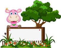Cute hippo cartoon with blank sign in garden Royalty Free Stock Photo