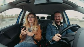 Cute hipster couple drives car at roadtrip. Happy and excited smiling just married couple, drive car during vacation or holiday road trip, smie and point out of stock footage