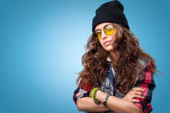 Cute hipster girl with curly hair wearing black beanie hat posing at the camera with crossed arms. royalty free stock photo