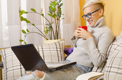 Cute hipster girl drinking coffee and networking at home Royalty Free Stock Images