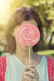 Cute hipster girl holding a big lollipop Royalty Free Stock Photo
