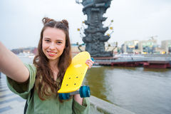 Cute hipster girl makihg selfie with skateboard outdoors in sunset light. Active sporty woman having fun in skate park. Royalty Free Stock Photos