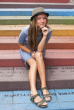 Cute hipster girl sitting on colorful steps on the street. Stock Image