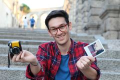 Cute hipster male holding retro camera and instant film picture stock photography