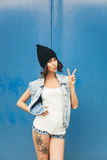Cute hipster teenage girl with black beanie hat and tattoo on leg Royalty Free Stock Images