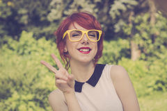 Cute hipster teenage girl showing peace sign Stock Photo