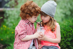 Cute hipsters drinking cocktail in park. Photo of two cute hipsters drinking cocktail in park Stock Image