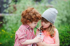 Cute hipsters drinking cocktail in park. Photo of two cute hipsters drinking cocktail in park Stock Photography
