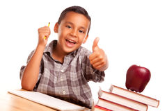 Cute Hispanic Boy with Books, Apple and Pencil. Adorable Hispanic Boy Gives His Thumbs Up With Books, Apple, Pencil and Paper Isolated on a White Background Royalty Free Stock Photography
