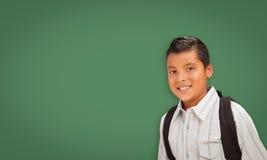 Cute Hispanic Boy In Front of Blank Chalk Board stock photo