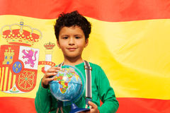 Cute Hispanic boy learn geography with globe. Spanish flag behind Stock Photography