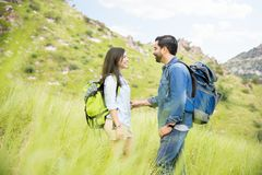Attractive Latin couple hiking. Cute Hispanic couple hiking in a park enjoying the afternoon together Royalty Free Stock Images