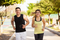 Cute Hispanic couple jogging together. Good looking young Hispanic couple jogging together at a park on a sunny day and smiling Stock Photos