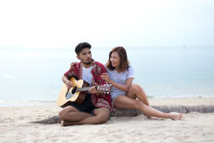 Cute hispanic couple playing guitar serenading on beach stock image