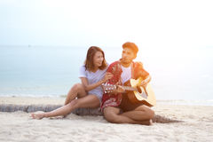Cute hispanic couple playing guitar serenading on beach stock photos