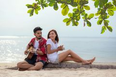 Cute hispanic couple playing guitar serenading on beach in love and embrace, happy and relax outdoor on the sand. stock images