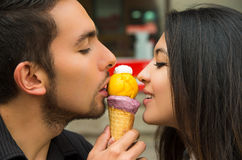 Cute hispanic couple sharing ice cream cone and Royalty Free Stock Photography