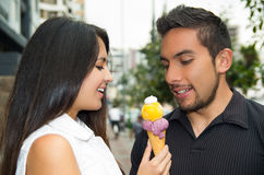 Cute hispanic couple sharing ice cream cone and Stock Image