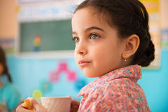 Cute hispanic girl with cup of milk at daycare. Cute little hispanic girl with cup of milk at daycare royalty free stock photos