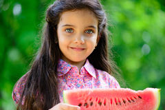Cute hispanic girl eating watermelon Stock Photo