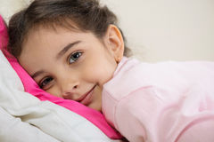 Cute hispanic girl lying in bed Stock Image