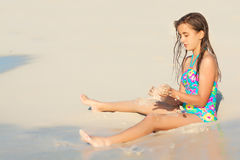 Cute hispanic girl playing with sand on a beach Royalty Free Stock Image