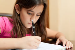 Cute hispanic girl studying at home Stock Photo
