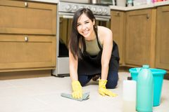 Cheerful house maid sweeping kitchen floor. Cute Hispanic housewife cleaning kitchen floor with rug and detergent looking at camera Royalty Free Stock Photo