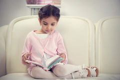 Cute hispanic little girl reading book on couch Royalty Free Stock Images