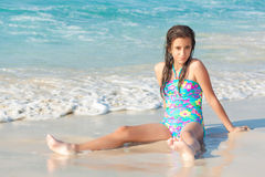 Cute hispanic teen sitting on a sunny beach in Cuba Stock Photography