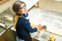 Cute Hispanic woman doing some woodwork. Gorgeous young Hispanic female carpenter doing some woodworking on her workshop royalty free stock image